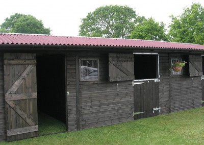 Black finish to the stable complex with a red onduline roof. A recent show unit.