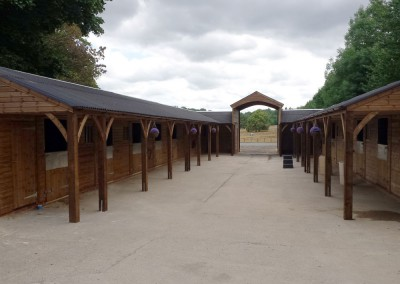 Large complex for a busy livery yard in Surrey, various size stables and a ride through arch to an arena.