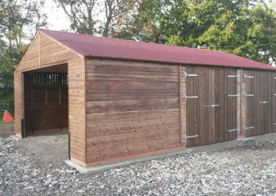 Large tractor store with open and enclosed storage , also with Yorkshire boarding to allow for ventilation and wind venting. Terracotta Onduline roof sheeting and steel framed doors with large adjustable hinges.