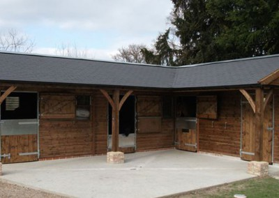 Bespoke stable complex with 5ft roof overhang. Posts with feature gallows brackets and brick plinth.