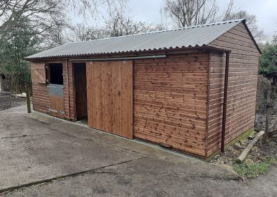 A delightful stable and store unit with a sliding door and fiber cement roof made to fit the space available for RDA.