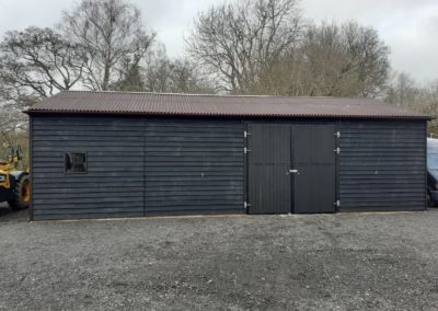A large 12m x 6m x 3m to eaves barn with black feather edge cladding and large pair of metal framed hinged doors for large machinery access. Brown Onduline roof and ridge cappings