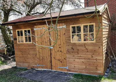 Attractive store shed with cottage windows and shingle roof. Double doors make putting ride on mowers or garden furniture away easy.