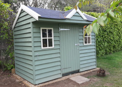 Green weatherboard cladding to this rather smart garden store. All standing on a suspended steel plinth without the need for any concrete!